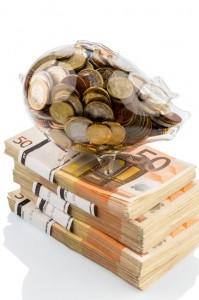 Festgeld Vergleich: Sparschwein voller Münzen steht auf einem Bündel Fünfzig Euro Scheine